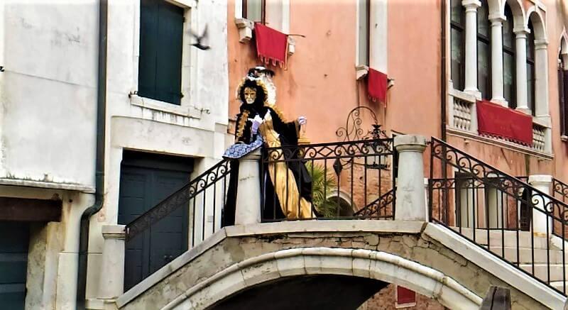 ヴェネツィア、カーニバルの写真。橋の上にたたずむ仮装姿の人。